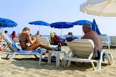 Juli 2017 - folket vilar på deckchairs i skuggan av strandparaplyer på Cleopatra Beach Alanya, Turkiet Arkivbild