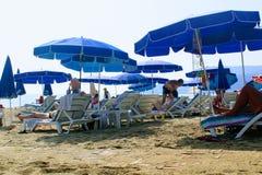 Juli 2017 - folket vilar på deckchairs i skuggan av strandparaplyer på Cleopatra Beach Alanya, Turkiet Arkivfoton