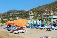 Juli 2017 - folket vilar på deckchairs i skuggan av strandparaplyer på Cleopatra Beach Alanya, Turkiet Arkivfoto