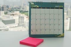 Juli 2018 kalender med åtlöje upp postiten för påminnelsemeddelande Arkivbild