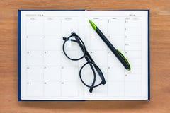 Juli-Kalenderseite des Tagebuchplanerbuches offene mit Gläsern und Stift auf Th Lizenzfreies Stockfoto
