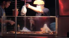 01 Juli, 2018 Macao De verkoper van het straatvoedsel Aziatische kerels die voor voedsel bij nacht winkelen stock video