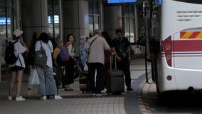 15 Juli, 2018 Macao Kina Passagerare får av från bussen och väljer upp bagage på flygplatsen arkivfilmer