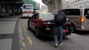 15 Juli, 2018 Macao Kina Passagerare får av från taxien och väljer upp bagage på flygplatsen stock video