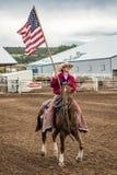18. Juli 2017 NORWOOD COLORADO - Cowboy beginnt Rodeo mit US-Flagge bei San Miguel Basin Rodeo, San Patriotisch, West stockbilder