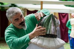 15 Juli 2017 Ploiesti Roemenië, Middeleeuws festival - slotenmaker die pantserhelm herstellen Stock Fotografie