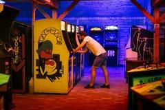 25. Juli 2017 - Prag, Tschechische Republik: Junger Mann mit Kappe spielt begeistert einen alten Säulengangvideospiel Pac-Mann II Lizenzfreie Stockfotografie
