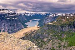 22. Juli 2015: Reisender am Rand von Trolltunga, Norwegen Lizenzfreie Stockfotografie