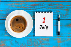 Juli 1st dag av månaden 1, kalender på affärsarbetsplatsbakgrund med morgonkaffekoppen sommar för snäckskal för sand för bakgrund Royaltyfri Fotografi