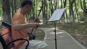 25 Juli, 2018 Suzhoustad, China De volwassen Chinese mens speelt een erhu, twee-stringed gebogen fiddle in het park Erhu is stock footage