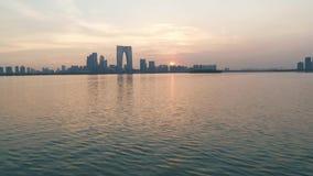 27 Juli, 2018 Suzhoustad, China Luchthommelvlucht over Jinji-Meerwaterspiegel op de zonsondergang Moderne gebouwen stock videobeelden