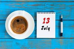 13. Juli Tag 13 des Monats, Kalender auf blauem Holztischhintergrund mit MorgenKaffeetasse Seashells gestalten auf Sandhintergrun Lizenzfreie Stockfotografie