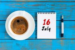 16. Juli Tag 16 des Monats, Kalender auf blauem Holztischhintergrund mit MorgenKaffeetasse Seashells gestalten auf Sandhintergrun Lizenzfreie Stockfotografie