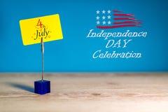 Juli 4th Bild av den juli 4 kalendern på liten gul etikett på blå bakgrund field treen Tomt avstånd för text Royaltyfri Fotografi