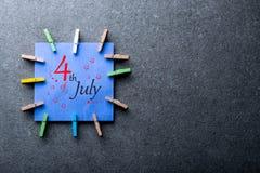 Juli 4th Bild av den juli 4 kalendern på mörk bakgrund field treen Tomt avstånd för text Gataclownen hälsar folk Arkivbilder
