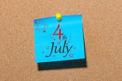 Juli 4th Bilden av den juli 4 kalendern på blått papper klämde fast till corkboardbakgrund field treen Tomt avstånd för text Arkivfoton