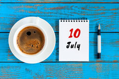 Juli 10th Dag 10 av månaden, kalender på blå trätabellbakgrund med morgonkaffekoppen sommar för snäckskal för sand för bakgrundsb Royaltyfria Foton