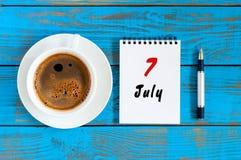 Juli 7th Dag 7 av månaden, kalender på blå trätabellbakgrund med morgonkaffekoppen sommar för snäckskal för sand för bakgrundsbeg Arkivfoton