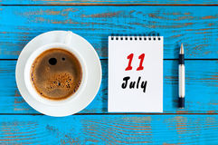 Juli 11th Dag 11 av månaden, kalender på blå trätabellbakgrund med morgonkaffekoppen sommar för snäckskal för sand för bakgrundsb Fotografering för Bildbyråer