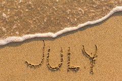 Juli - Wort gezeichnet auf den Sandstrand mit der weichen Welle Lizenzfreie Stockbilder