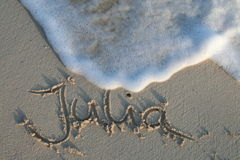 Julia - name in the sand. Julia - common international first name, written in the sand. Wave coming close Royalty Free Stock Images