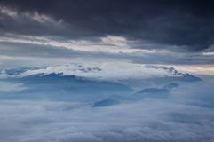 Julian Alps blanketed in sea of low level clouds and autumn fog. Jagged ridges of Julian Alps, Sava valley and Pokljuka plateau blanketed in sea of low level Stock Image