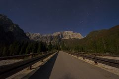 Julien Alps mountain scene under the moonlight. Night road in foreground Stock Photo