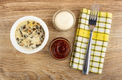 Julienne с цыпленком, грибом в шаре, шарами с кетчуп и майонезом, вилкой на салфетке на таблице r стоковое фото