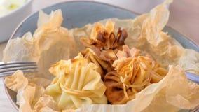 Julienne ha cotto in pasta è servito su un piatto sulla carta del panettiere con tè e burro Vista laterale stock footage