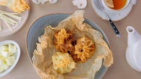 Julienne ha cotto in pasta è servito su un piatto sulla carta del panettiere con tè e burro Vista del primo piano video d archivio