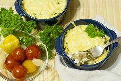 Julienne with mushrooms and cream. Mushroom and cheese gratin in ceramic bowls, on wooden background Stock Photography