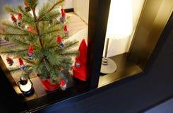 Julinre på fönstret En liten konstgjord julgran med leksaker och stearinljus arkivbilder