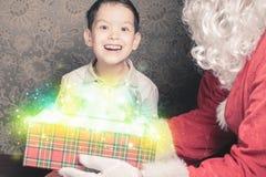 Julinspiration! Lycklig chockad pojke som förvånas för att se jultomten Fotografering för Bildbyråer