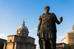 Julius Caesar statue. On Fori Imperiali with church of Santi Luca e Martina in background Royalty Free Stock Image