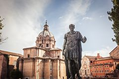 Julius Caesar statue in Rome. Julius Caesar statue with church of Saint Luca e Martina on the background - a bronze copy of the statue in the Capitol Royalty Free Stock Image