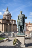 Julius Caesar Statue in Rome Italy. Julius Caesar statue with a wreath at its base and chapel dome and blue sky in the background.  Located near the Roman Forum Royalty Free Stock Photos