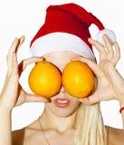 Juljulhälsningar med apelsinflickablondinen i ett rött Royaltyfri Fotografi