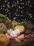 Juljulljus och prydnader, tangerin och muttrar på en mörk bakgrund med lightscandles och prydnader över mörkerbac Royaltyfri Fotografi