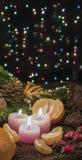Juljulljus och prydnader, tangerin och muttrar på en mörk bakgrund med lightscandles och prydnader över mörkerbac Royaltyfria Bilder