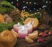 Juljulljus och prydnader, tangerin och muttrar på en mörk bakgrund med lightscandles och prydnader över mörkerbac Arkivbilder