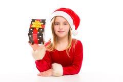 Juljultomten lurar lyckligt upphetsat för flicka med bandgåvan Royaltyfri Fotografi