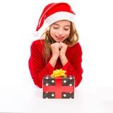 Juljultomten lurar lyckligt upphetsat för flicka med bandgåvan Royaltyfri Foto