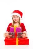 Juljultomten lurar lyckligt upphetsat för flicka med bandgåvor Arkivbild