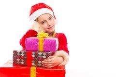 Juljultomten lurar lyckligt upphetsat för flicka med bandgåvor Arkivfoto