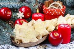 Julkakor i stjärnaform, röda äpplen och grön gran Arkivfoto