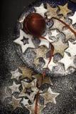 Julkakor som strilas av socker på plattan med det röda äpplet. royaltyfri bild