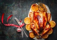Julkalkon med gaffeln, kniven och festlig garnering på mörk lantlig bakgrund arkivfoto