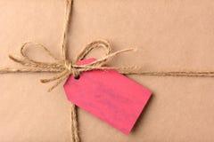 Julklapp med den röda gåvaetikettscloseupen Arkivfoto