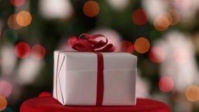 Julklapp som rotera av att blinka, tänder framme på xmas-träd stock video