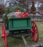 Julklappar i antik vagn med det suddiga julträdet i backround Arkivbild